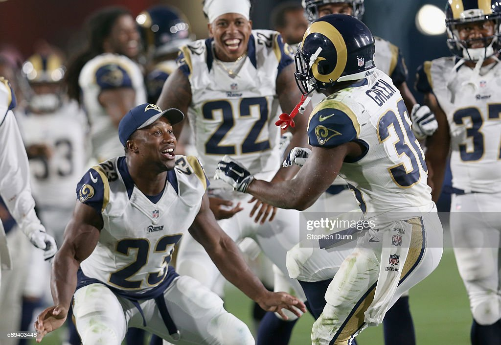 Running back Aaron Green #36 of the Los Angeles Rams is greeted by teammates including Benny Cunningham #23 after scoring the winning touchdown in the fourth quarter against the Dallas Cowboys at the Los Angeles Coliseum during preseason on August 13, 2016 in Los Angeles, California. The Rams won 28-24.
