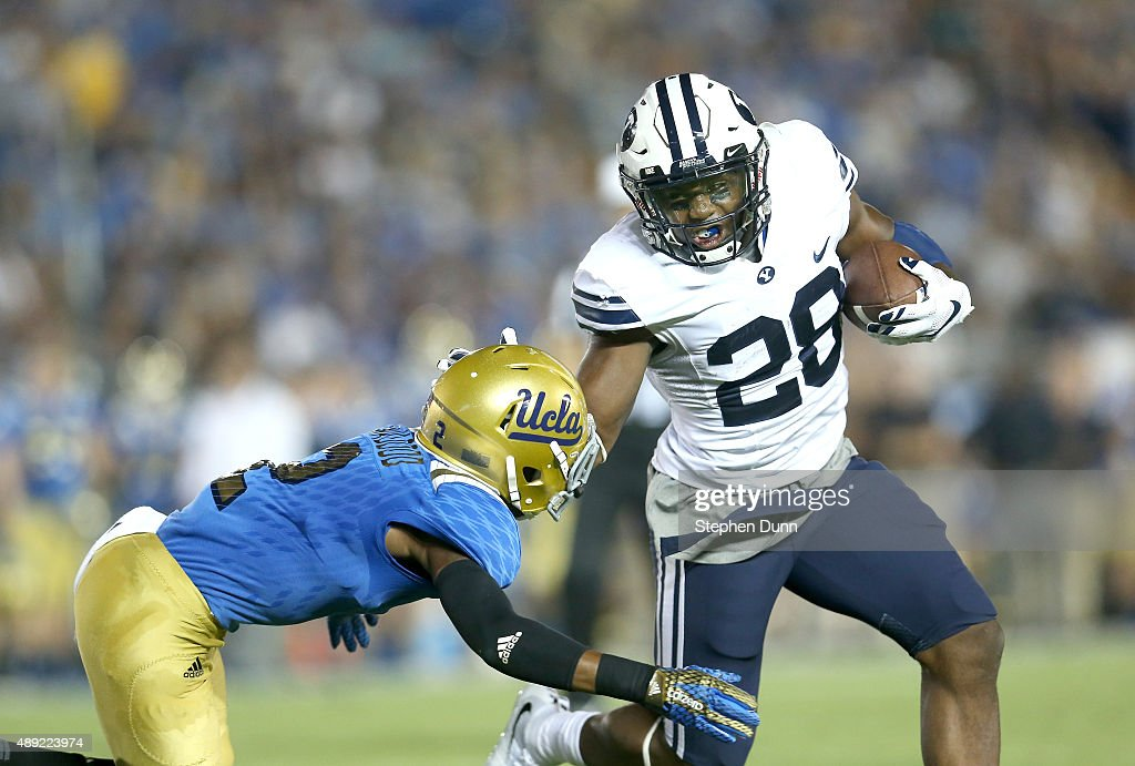 Running back Adam Hine of the BYU Cougars stiff arms defensive back Jaleel Wadood of the UCLA Bruins as carries the ball on a seven yard touchdown...