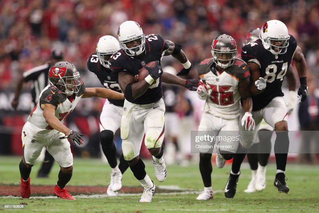 Running back Adrian Peterson #23 of the Arizona Cardinals rushes the football past cornerback Brent Grimes #24 and defensive back Robert McClain #36 of the Tampa Bay Buccaneers during the second half of the NFL game at the University of Phoenix Stadium on October 15, 2017 in Glendale, Arizona. The Cardinals defeated the Buccaneers 38-33.