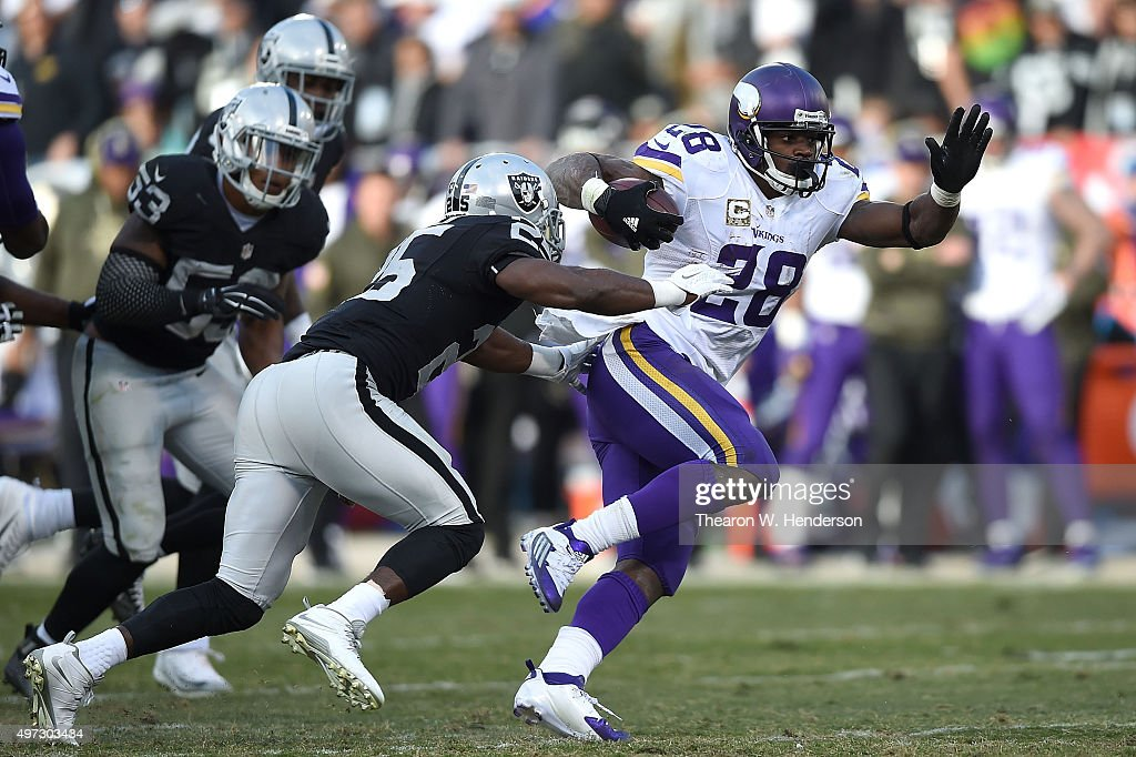Running back Adrian Peterson of the Minnesota Vikings breaks away from cornerback DJ Hayden of the Oakland Raiders in the fourth quarter at Oco...