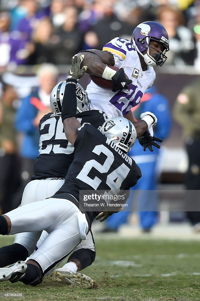 Running back Adrian Peterson of the Minnesota Vikings breaks the tackle of free safety Charles Woodson of the Oakland Raiders and running back...