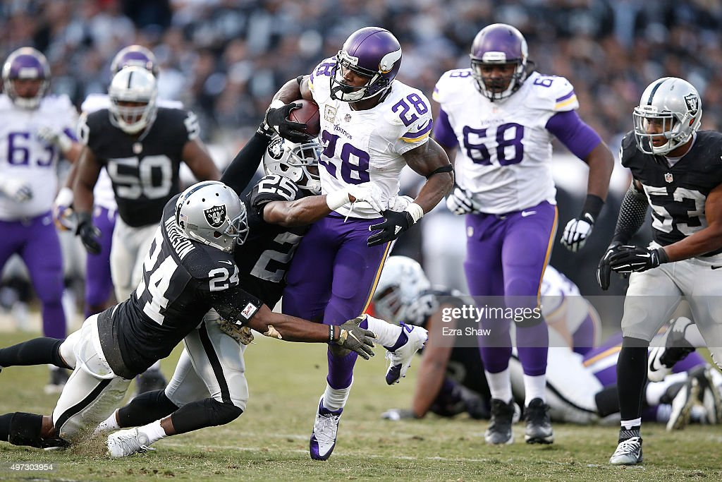 Running back Adrian Peterson of the Minnesota Vikings breaks the tackle of free safety Charles Woodson of the Oakland Raiders and running back DJ...