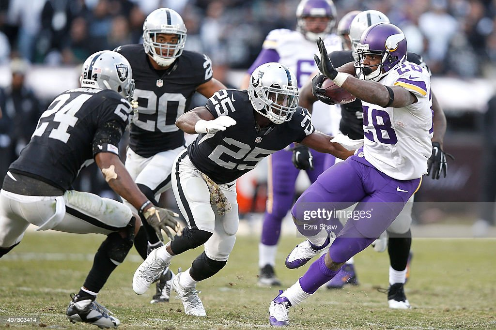 Running back Adrian Peterson of the Minnesota Vikings defends against the tackle of free safety Charles Woodson of the Oakland Raiders and running...