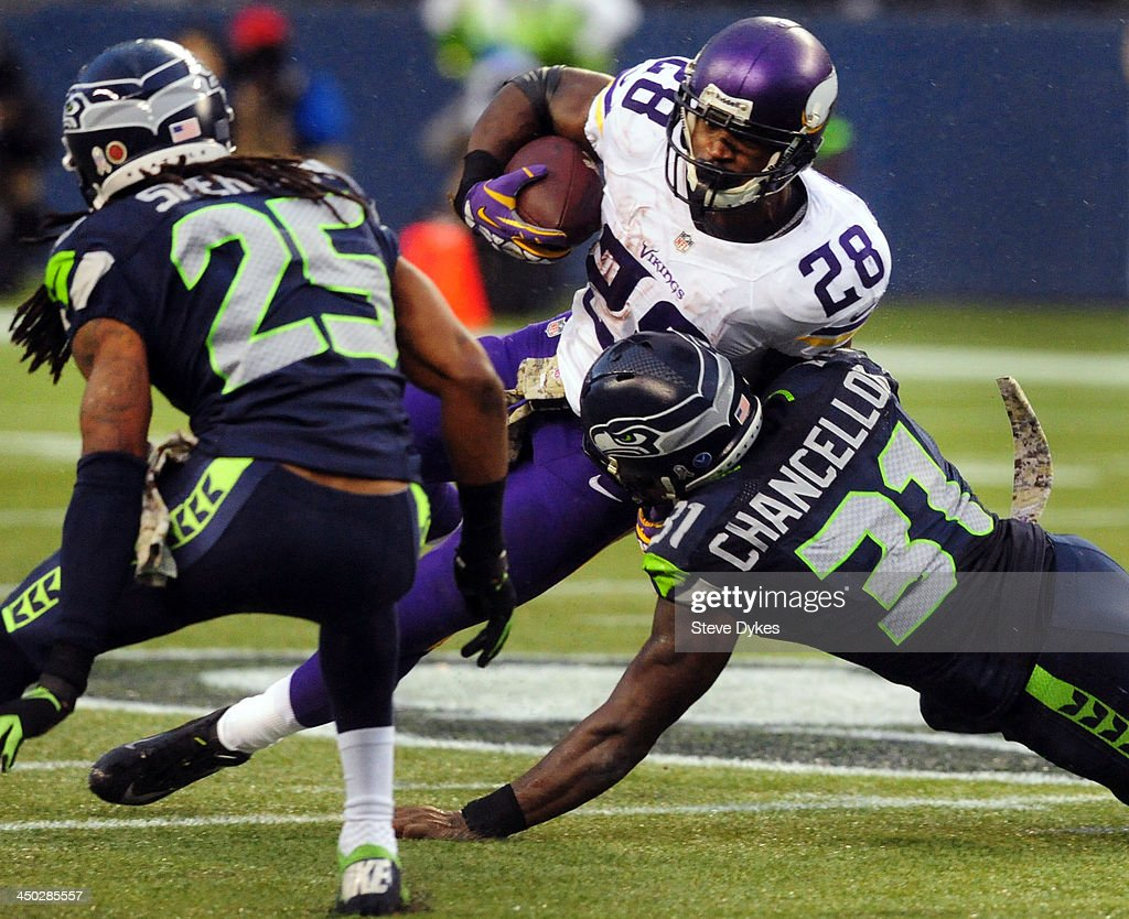 Running back Adrian Peterson #28 of the Minnesota Vikings is tackled by strong safety Kam Chancellor #31 of the Seattle Seahawks during the third quarter of the game at CenturyLink Field on November 17, 2013 in Seattle,Wa. The Seahawks won the game 41-20.