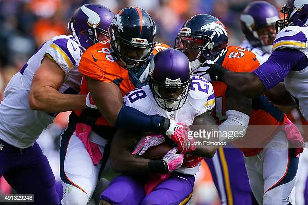 Running back Adrian Peterson of the Minnesota Vikings is wrapped up by defensive end Vance Walker and inside linebacker Brandon Marshall of the...