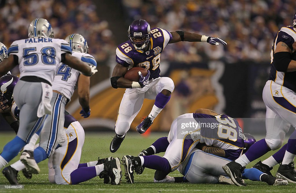 Running back Adrian Peterson #28 of the Minnesota Vikings jumps through a hole while carrying the ball against the Detroit Lions during the second half at Hubert H. Humphrey Metrodome on September 26, 2010 in Minneapolis, Minnesota. The Vikings defeated the Lions 24-10.