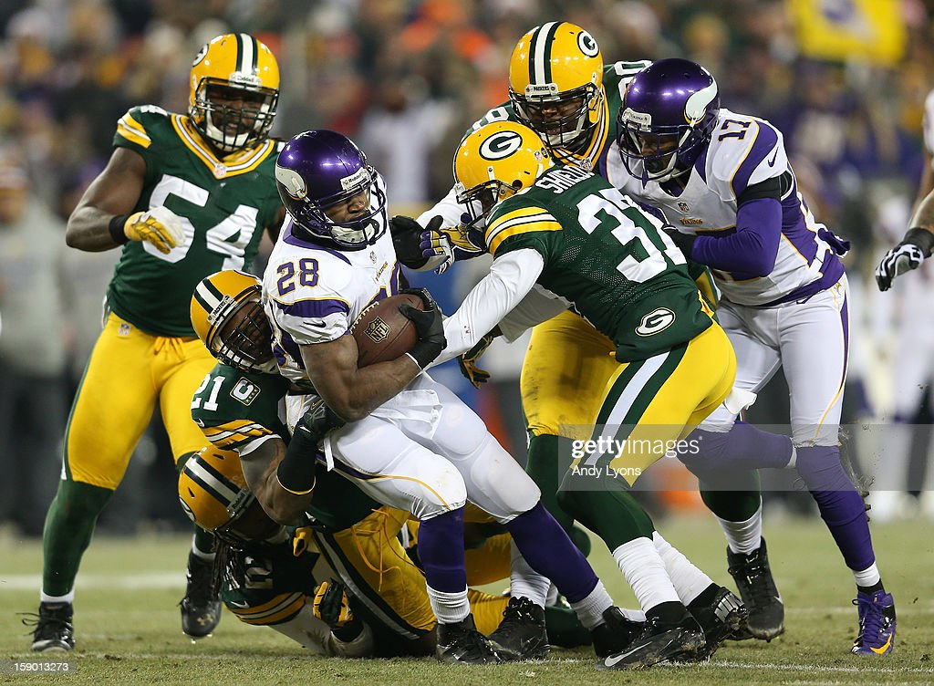 Running back Adrian Peterson #28 of the Minnesota Vikings runs the ball as he is tackled by strong safety Charles Woodson #21 and cornerback Sam Shields #37 of the Green Bay Packers in the first quarter during the NFC Wild Card Playoff game at Lambeau Field on January 5, 2013 in Green Bay, Wisconsin.
