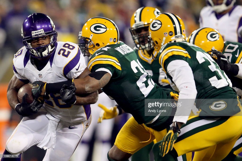 Running back Adrian Peterson #28 of the Minnesota Vikings runs the ball as he is hit by strong safety Charles Woodson #21 of the Green Bay Packers in the first quarter during the NFC Wild Card Playoff game at Lambeau Field on January 5, 2013 in Green Bay, Wisconsin.