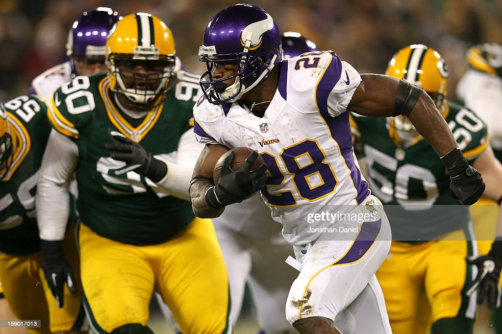 Running back Adrian Peterson #28 of the Minnesota Vikings runs the ball in front of nose tackle B.J. Raji #90 of the Green Bay Packers in the second half during the NFC Wild Card Playoff game at Lambeau Field on January 5, 2013 in Green Bay, Wisconsin.