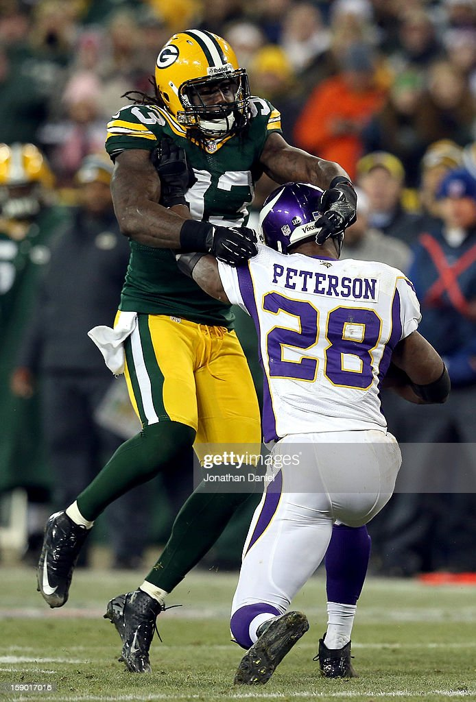 Running back Adrian Peterson #28 of the Minnesota Vikings runs the ball as he is hit by outside linebacker Erik Walden #93 of the Green Bay Packers in the second half during the NFC Wild Card Playoff game at Lambeau Field on January 5, 2013 in Green Bay, Wisconsin.