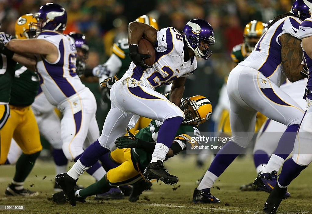 Running back Adrian Peterson #28 of the Minnesota Vikings runs the ball against safety Charles Woodson #21 of the Green Bay Packers in the first quarter during the NFC Wild Card Playoff game at Lambeau Field on January 5, 2013 in Green Bay, Wisconsin.