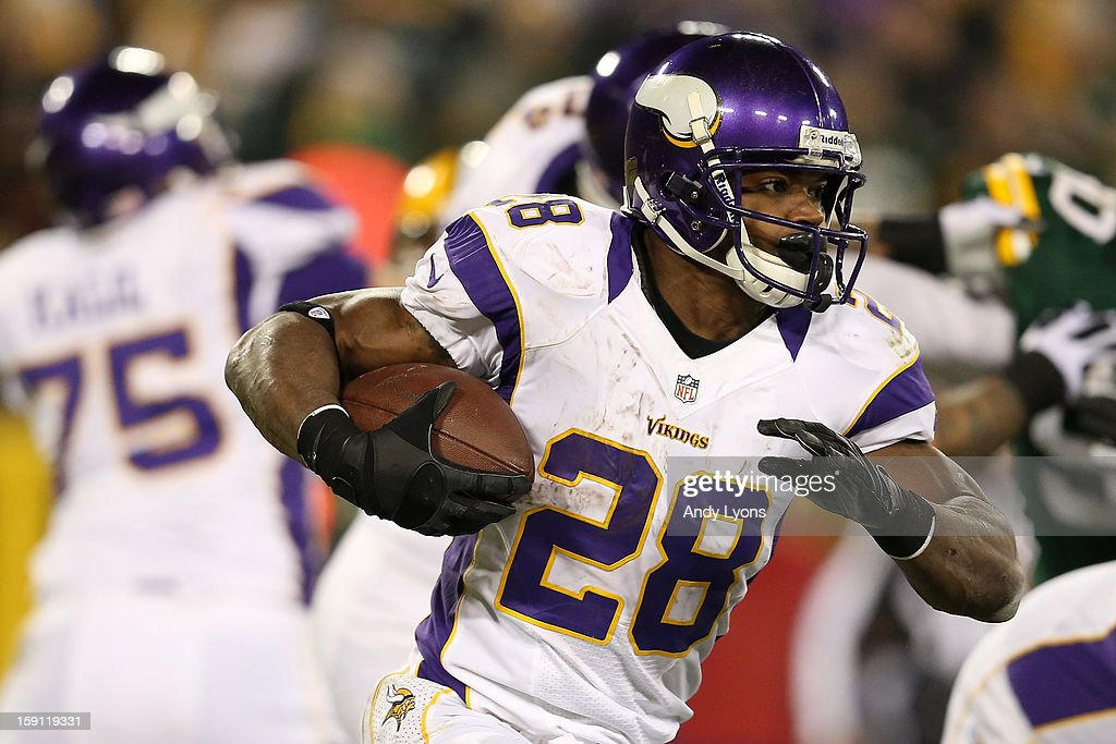 Running back Adrian Peterson #28 of the Minnesota Vikings runs the ball against the Green Bay Packers during the NFC Wild Card Playoff game at Lambeau Field on January 5, 2013 in Green Bay, Wisconsin.