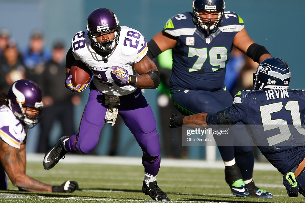Running back <a gi-track='captionPersonalityLinkClicked' href=/galleries/search?phrase=Adrian+Peterson+-+American+Football+Player+-+Minnesota+Vikings&family=editorial&specificpeople=210807 ng-click='$event.stopPropagation()'>Adrian Peterson</a> #28 of the Minnesota Vikings rushes against defensive end <a gi-track='captionPersonalityLinkClicked' href=/galleries/search?phrase=Bruce+Irvin&family=editorial&specificpeople=7355087 ng-click='$event.stopPropagation()'>Bruce Irvin</a> #51 of the Seattle Seahawks at CenturyLink Field on November 17, 2013 in Seattle, Washington. The Seahawks defeated the Vikings 41-20.