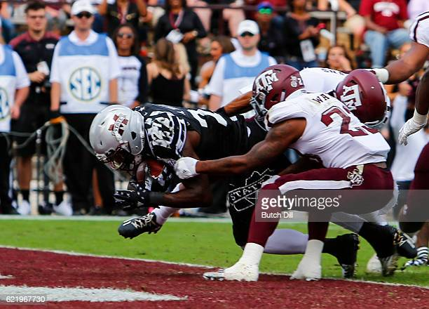 Running back Aeris Williams of the Mississippi State Bulldogs dives in for a touchdown as defensive back Armani Watts of the Texas AM Aggies tries to...
