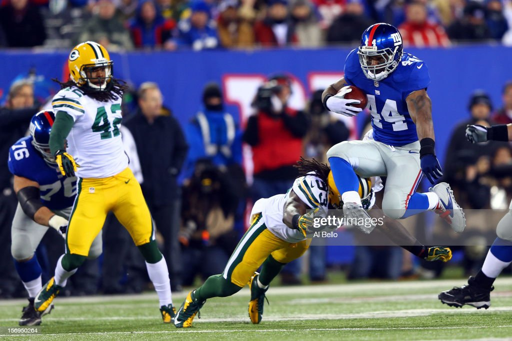 Running back Ahmad Bradshaw #44 of the New York Giants jumps over the tackle of outside linebacker Erik Walden #93 of the Green Bay Packers at the begining of a 59 yard catch and run at MetLife Stadium on November 25, 2012 in East Rutherford, New Jersey.