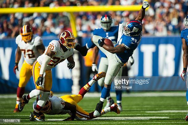 Running back Ahmad Bradshaw of the New York Giants looses his balance after being tripped by free safety Madieu Williams of the Washington Redskins...