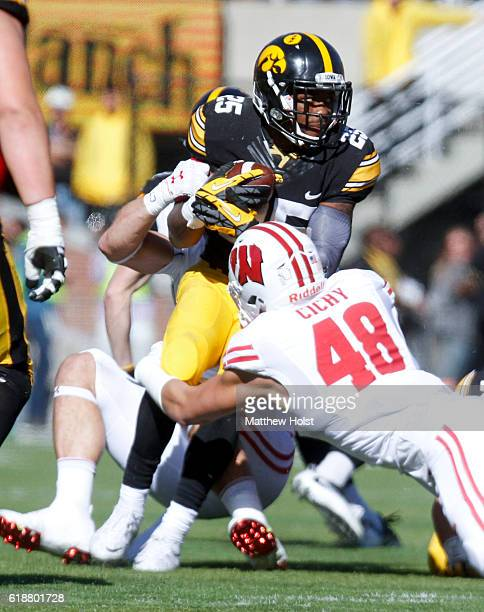 Running back Akrum Wadley of the Iowa Hawkeyes is brought down during the second quarter by linebackers Vince Biegel and Jack Cichy of the Wisconsin...