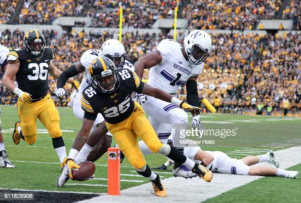 Running back Akrum Wadley of the Iowa Hawkeyes rushes in for a touchdown during the first quarter in front of cornerback Montre Hartage and...