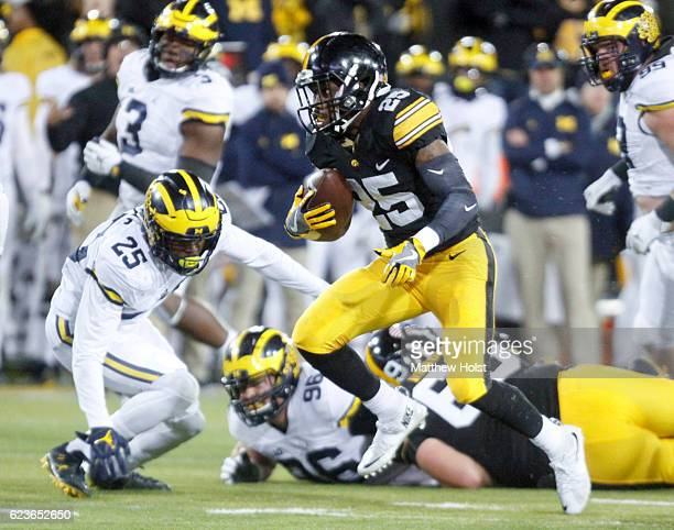 Running back Akrum Wadley of the Iowa Hawkeyes rushes up the field in front of safety Dymonte Thomas of the Michigan Wolverines during the third...