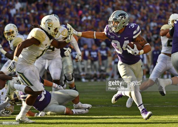Running back Alex Barnes of the Kansas State Wildcats rushes up field against free safety Davion Hall of the Baylor Bears during the second half on...