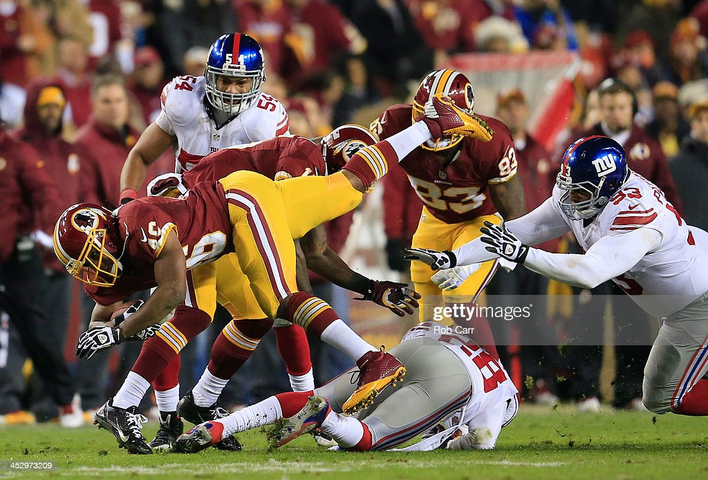 Running back Alfred Morris of the Washington Redskins is tackled by Jayron Hosley and defensive tackle Mike Patterson of the New York Giants during...