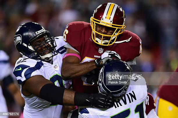 Running back Alfred Morris of the Washington Redskins is tackled by defensive tackle Brandon Mebane and outside linebacker Bruce Irvin of the Seattle...