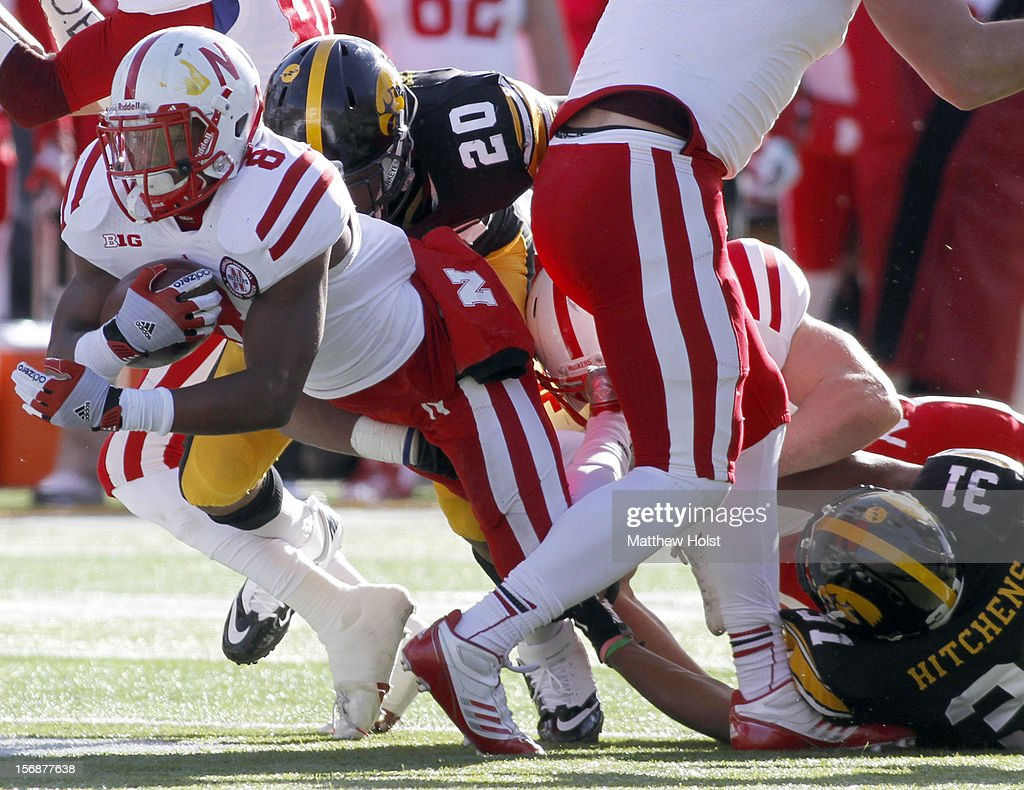 Running back Ameer Abdullah #8 of the Nebraska Cornhusker is brought down during the first quarter by Christian Kirksey #20 of the Iowa Hawkeyes on November 23, 2012 at Kinnick Stadium in Iowa City, Iowa. Nebraska defeated Iowa 13-7.