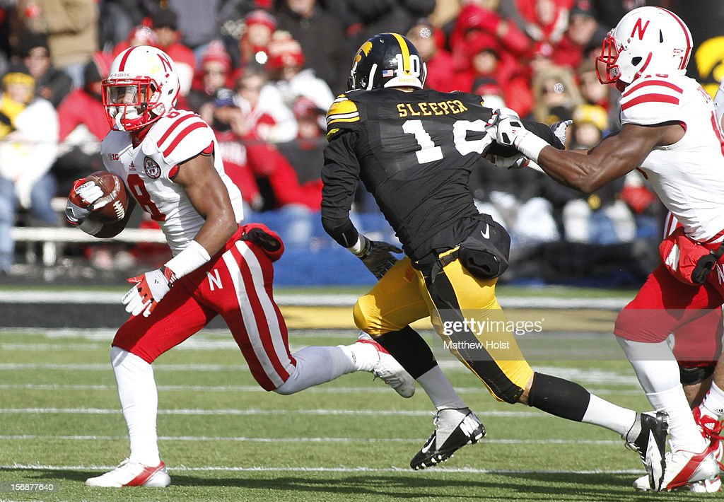 Running back Ameer Abdullah #8 of the Nebraska Cornhusker rushes up field during the second quarter in front of defensive back Collin Sleeper #10 of the Iowa Hawkeyes on November 23, 2012 at Kinnick Stadium in Iowa City, Iowa. Nebraska defeated Iowa 13-7.