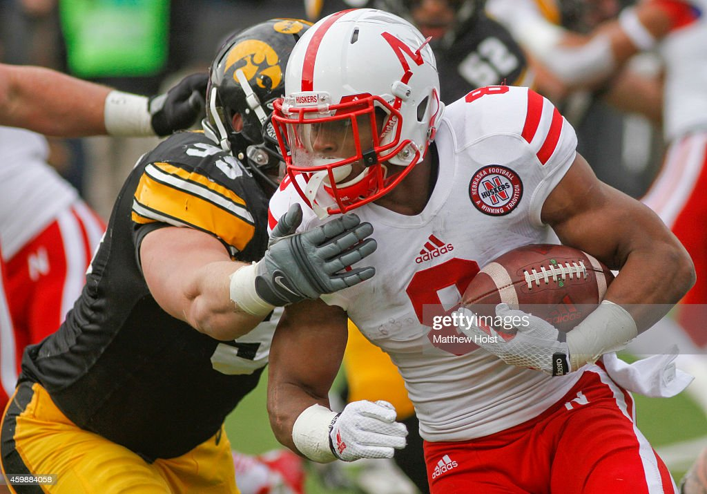Running back <a gi-track='captionPersonalityLinkClicked' href=/galleries/search?phrase=Ameer+Abdullah&family=editorial&specificpeople=8199967 ng-click='$event.stopPropagation()'>Ameer Abdullah</a> #8 of the Nebraska Cornhuskers breaks a tackle by defensive lineman Drew Ott #95 of the Iowa Hawkeyes, in the second quarter, on November 28, 2014 at Kinnick Stadium, in Iowa City, Iowa.