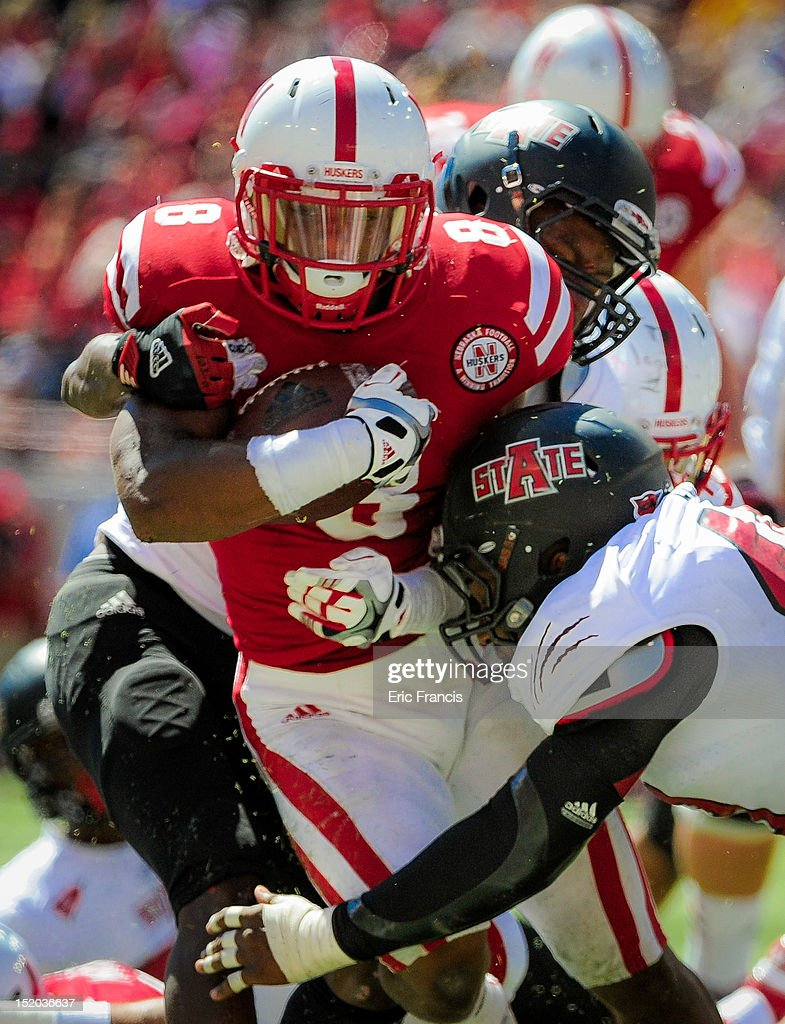 Running back Ameer Abdullah #8 of the Nebraska Cornhuskers is wrapped up by linebacker Nathan Herrold #40 and defensive back Sterling Young #11 of the Arkansas State Red Wolves during their game at Memorial Stadium on September 15, 2012 in Lincoln, Nebraska. Nebraska won 42-13.
