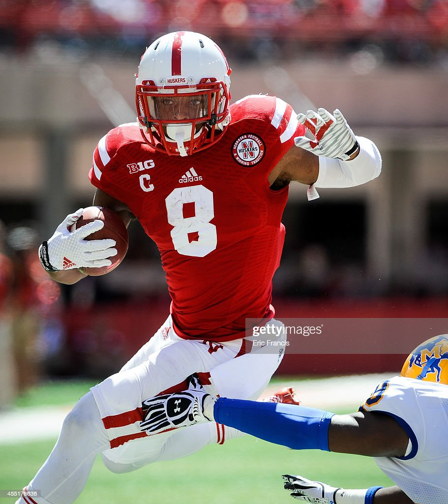 Running back <a gi-track='captionPersonalityLinkClicked' href=/galleries/search?phrase=Ameer+Abdullah&family=editorial&specificpeople=8199967 ng-click='$event.stopPropagation()'>Ameer Abdullah</a> #8 of the Nebraska Cornhuskers runs past linebacker Ashari Goins #49 of the McNeese State Cowboys during their game at Memorial Stadium on September 6, 2014 in Lincoln, Nebraska. Nebraska defeated McNeese State 31-24.