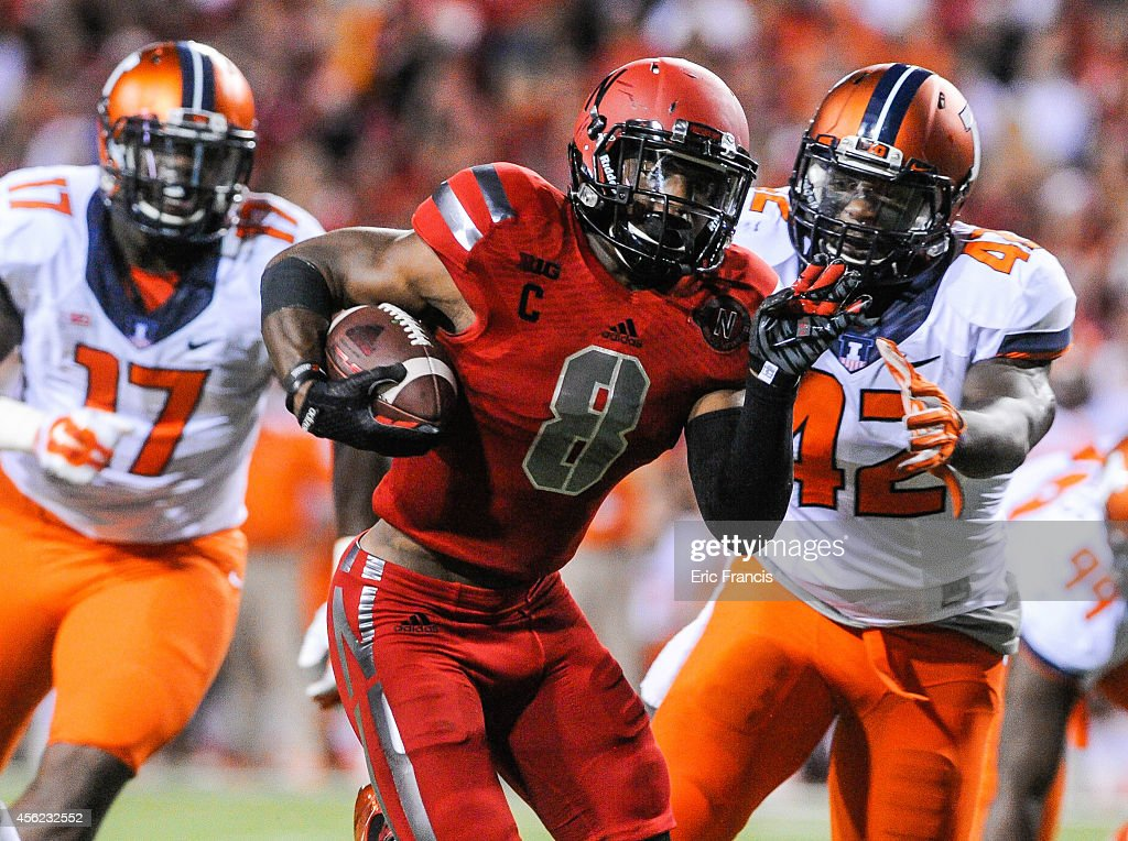 Running back <a gi-track='captionPersonalityLinkClicked' href=/galleries/search?phrase=Ameer+Abdullah&family=editorial&specificpeople=8199967 ng-click='$event.stopPropagation()'>Ameer Abdullah</a> #8 of the Nebraska Cornhuskers runs past linebacker Ralph Cooper #42 and defensive lineman <a gi-track='captionPersonalityLinkClicked' href=/galleries/search?phrase=Jihad+Ward&family=editorial&specificpeople=13613126 ng-click='$event.stopPropagation()'>Jihad Ward</a> #17 of the Illinois Fighting Illini during their game at Memorial Stadium on September 27, 2014 in Lincoln, Nebraska.