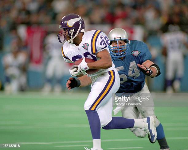 Running back Amp Lee of the Minnesota Vikings runs from linebacker Chris Spielman of the Detroit Lions during a game at the Pontiac Silverdome on...