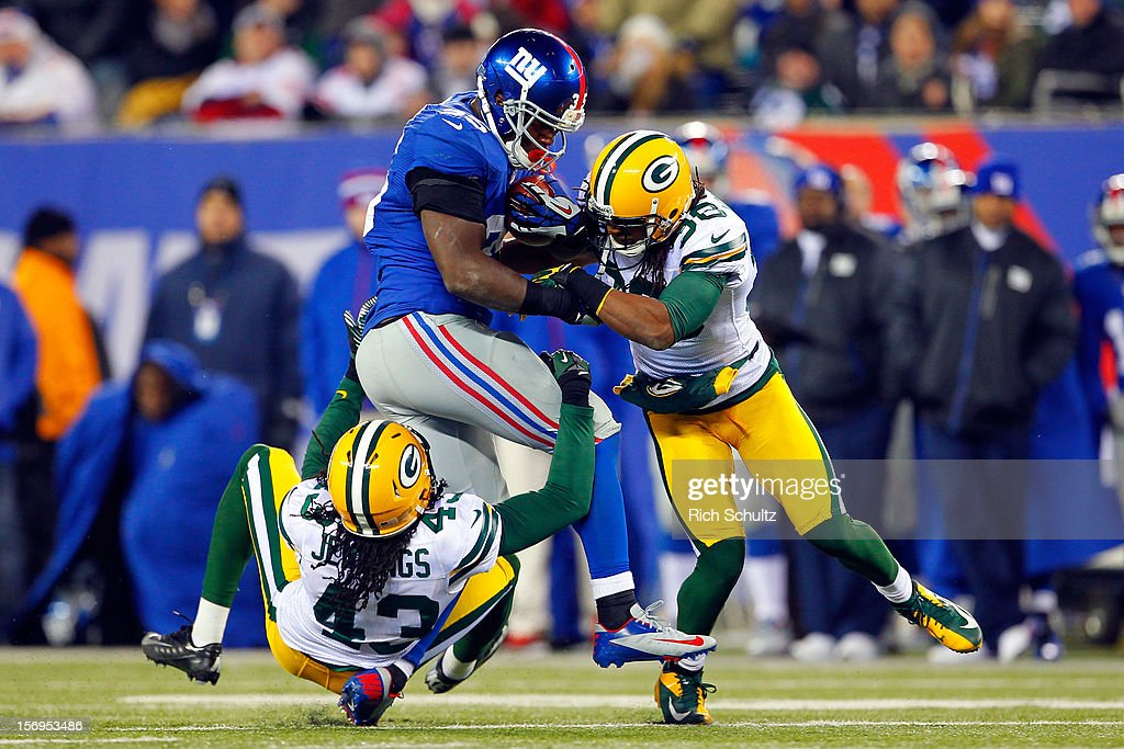 Running back Andre Brown #35 of the New York Giants hurts his leg while getting tackled by free safety M.D. Jennings #43 and cornerback Tramon Williams #38 of the Green Bay Packers in the fourth quarterat MetLife Stadium on November 25, 2012 in East Rutherford, New Jersey.