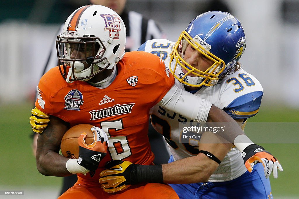 Running back Anthon Samuel of the Bowling Green Falcons is tackled by linebacker Vince Buhagiar of the San Jose State Spartans during the first half...