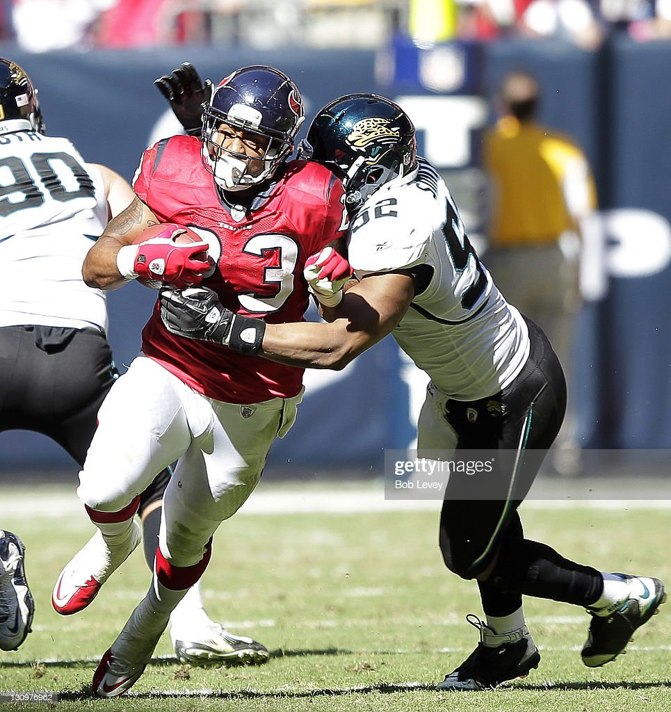 Running back <a gi-track='captionPersonalityLinkClicked' href=/galleries/search?phrase=Arian+Foster&family=editorial&specificpeople=2128663 ng-click='$event.stopPropagation()'>Arian Foster</a> #23 of the Houston Texans is tackled by linebacker <a gi-track='captionPersonalityLinkClicked' href=/galleries/search?phrase=Daryl+Smith&family=editorial&specificpeople=2097172 ng-click='$event.stopPropagation()'>Daryl Smith</a> #52 of the Jacksonville Jaguars at Reliant Stadium on October 30, 2011 in Houston, Texas.