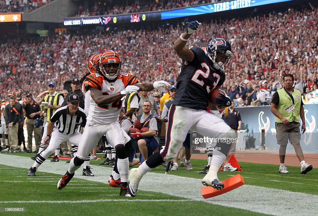 Running back <a gi-track='captionPersonalityLinkClicked' href=/galleries/search?phrase=Arian+Foster&family=editorial&specificpeople=2128663 ng-click='$event.stopPropagation()'>Arian Foster</a> #23 of the Houston Texans scores on an eight-yard touchdown run in the first quarter in front of cornerback Adam Jones #24 of the Cincinnati Bengals during their 2012 AFC Wild Card Playoff game at Reliant Stadium on January 7, 2012 in Houston, Texas.