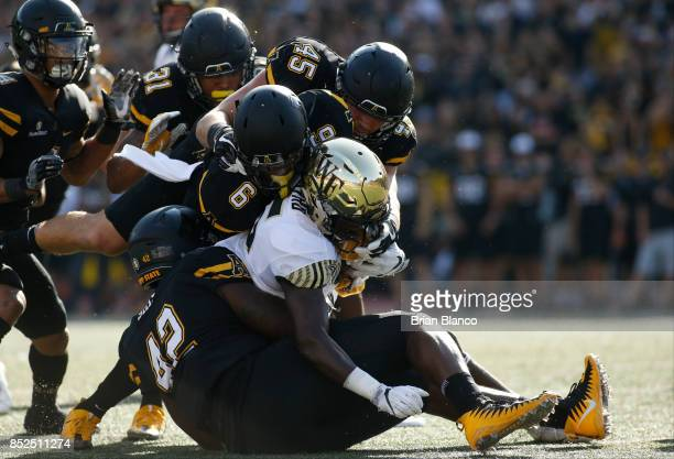 Running back Arkeem Byrd of the Wake Forest Demon Deacons is stopped by defensive back Desmond Franklin of the Appalachian State Mountaineers...
