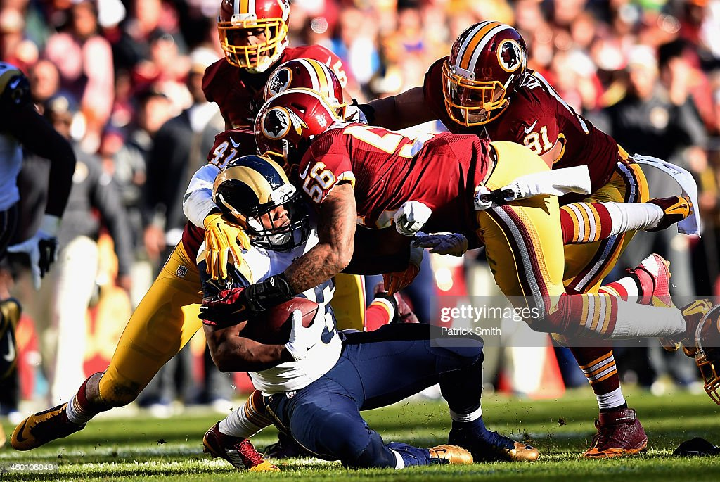 Running back Benny Cunningham of the St Louis Rams is tackled by strong safety Phillip Thomas of the Washington Redskins and inside linebacker Perry...
