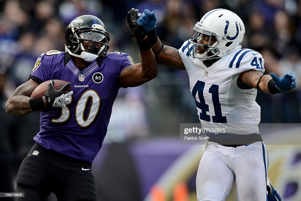 Running back Bernard Pierce #30 of the Baltimore Ravens eludes safety Antoine Bethea #41 of the Indianapolis Colts during the AFC Wild Card Playoff Game at M&T Bank Stadium on January 6, 2013 in Baltimore, Maryland.