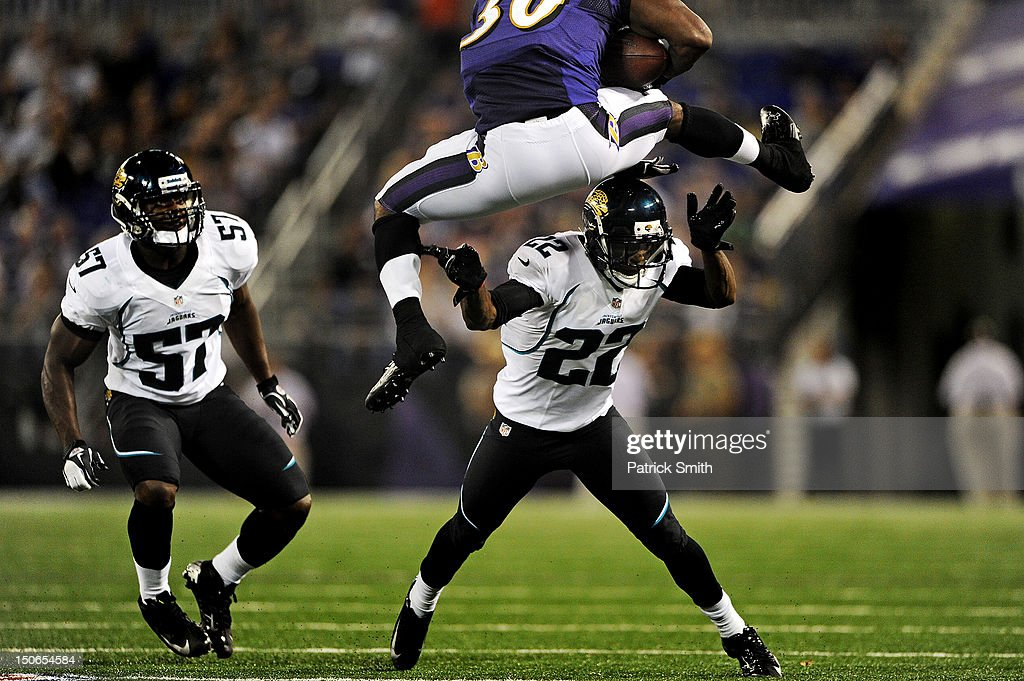 Running back Bernard Pierce #30 of the Baltimore Ravens leaps over cornerback Kevin Rutland #22 of the Jacksonville Jaguars and as his teammate linebacker Julian Stanford #57 of the Jacksonville Jaguars looks on during the third quarter at M&T Bank Stadium on August 23, 2012 in Baltimore, Maryland. The Baltimore Ravens won, 48-17.