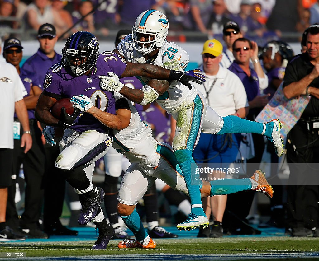 Running back Bernard Pierce #30 of the Baltimore Ravens picks up yardage as strong safety Reshad Jones #20 of the Miami Dolphins pursues during a game at Sun Life Stadium on December 7, 2014 in Miami Gardens, Florida.