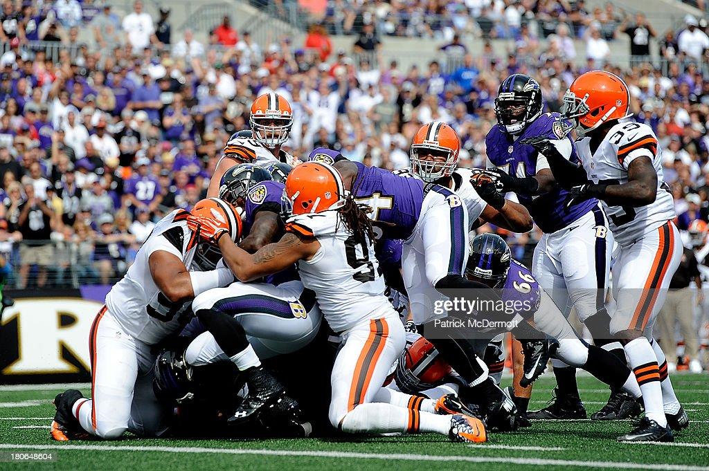 Running back Bernard Pierce #30 of the Baltimore Ravens pushes through the Cleveland Browns defense to score a touchdown during the second half of a game at M&T Bank Stadium on September 15, 2013 in Baltimore, Maryland.