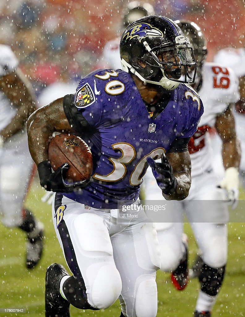 Running back Bernard Pierce #30 of the Baltimore Ravens rushes for a second quarter touchdown in the rain against the Tampa Bay Buccaneers during a preseason game at Raymond James Stadium on August 8, 2013 in Tampa, Florida.