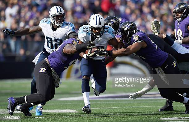 Running back Bishop Sankey of the Tennessee Titans rushes againt defensive end Chris Canty and outside linebacker Courtney Upshaw of the Baltimore...