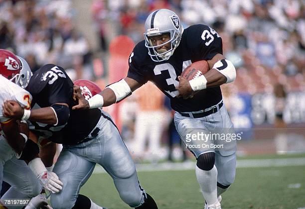Running back Bo Jackson of the Los Angeles Raiders carries the ball during a circa late 1980's NFL game against the Kansas City Chiefs Jackson played...