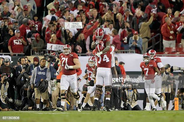 Running back Bo Scarbrough of the Alabama Crimson Tide celebrates with offensive lineman Cam Robinson after rushing for a 37yard touchdown during the...