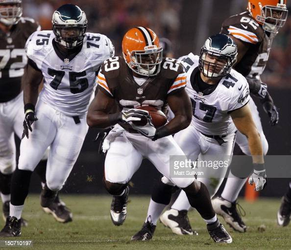 Running back Brandon Jackson of the Cleveland Browns runs the ball by defenders Vinny Curry and Ryan Rau of the Philadelphia Eagles at Cleveland...