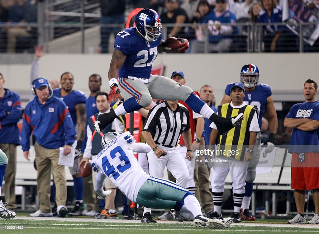 Running back Brandon Jacobs #27 of the New York Giants leaps over safety Gerald Sensabaugh #43 of the Dallas Cowboys in the first quarter at Cowboys Stadium on December 11, 2011 in Arlington, Texas.