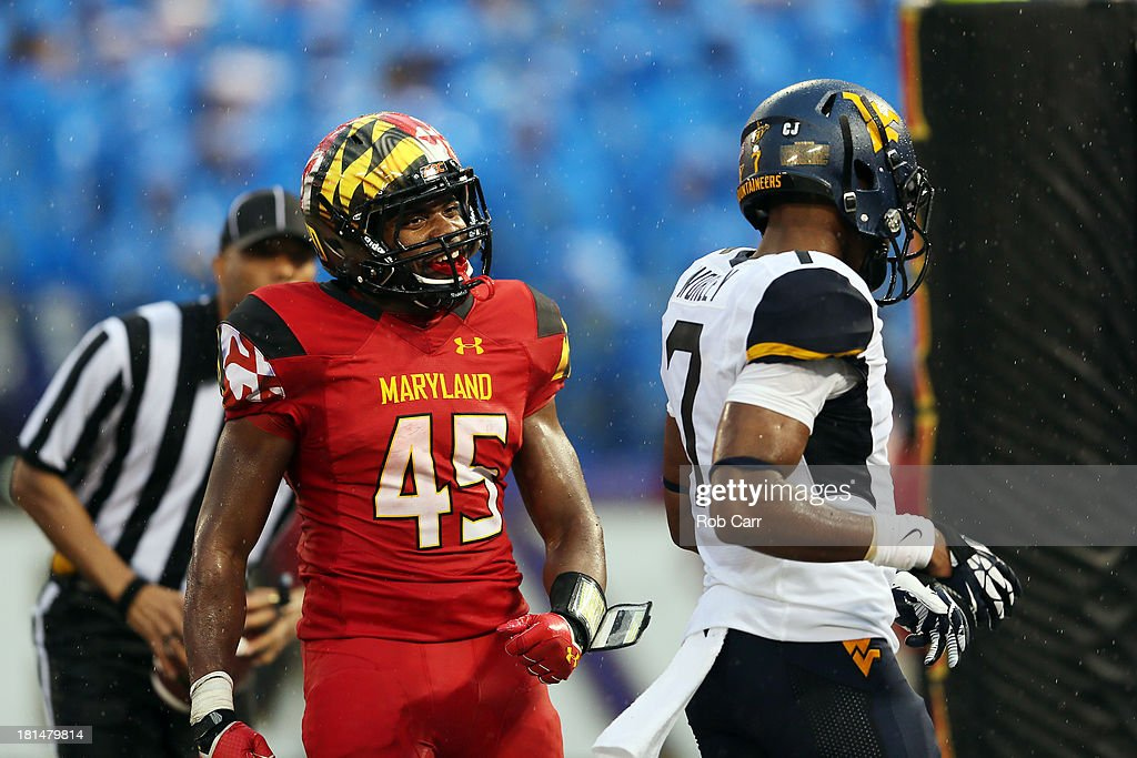 Running back Brandon Ross #45 of the Maryland Terrapins celebrates after scoring a fourth quarter touchdown in front of cornerback Daryl Worley #7 of the West Virginia Mountaineers at M&T Bank Stadium on September 21, 2013 in Baltimore, Maryland. Maryland won 37-0.